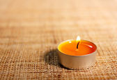 Burning orange candle placed on jute material — Stock fotografie