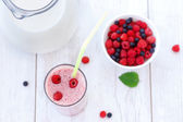 Raspberry and blueberry milkshake on white wooden table — Stock Photo