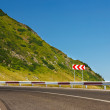 Royalty-Free Stock Photo: Safety sign on mountain road before a dangerous curve
