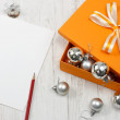 Orange gift box with silver christmas baubles — Stock Photo