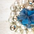 Top view of blue giftbox surrounded by silver baubles — Stock Photo