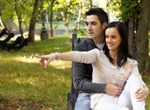 Portrait of smiling young couple sitting on a bench in park — Stock Photo