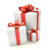 Three white gift boxes with red ribbon on white floor — Stok fotoğraf