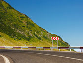 Safety sign on mountain road before a dangerous curve — Stock Photo