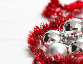 Christmas arrangement with silver baubles and red garland — Stock Photo