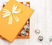 Orange Christmas gift box filled with silver baubles — Stock Photo