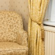 Stock Photo: Brown vintage armchair near retro curtain