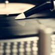 Old fashioned turntable playing a track from black vinyl — Stock Photo #18143131