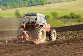 Photo of red tractor working the ground — Stock Photo