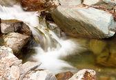 Beautiful cascade through mountain rocks — Stock Photo