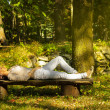 Woman with eyes closed relaxing on a bench in nature — Foto de Stock