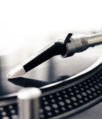 Old fashioned turntable playing a track from black vinyl — Stock Photo