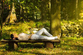 Woman with eyes closed relaxing on a bench in nature — Stock Photo