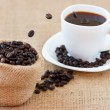 Coffee beans jumping into white cup — Stock Photo