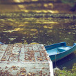 Blue boats on lake in autumn season — Stock Photo #26302411