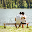 Young lovers sitting on wooden bench — Foto de Stock