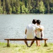 Young lovers sitting on wooden bench — Stock Photo