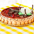 Round cake with cherry and biscuits on tablecloth — Stock Photo