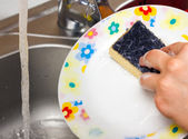 Woman using a yellow sponge to clean the plate — Stock Photo