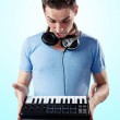 Deejay with headphones holding midi keyboard in hands — Stock Photo #30336251
