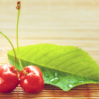 Two cherries placed near green leaf on bamboo tablecloth — Stock Photo