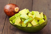 Chopped avocado fruit on brown wooden old table — Stock Photo