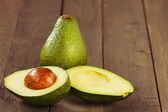 Avocado fruit on brown wooden old table — Stockfoto