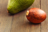 Avocado core on brown wooden old table — Stockfoto
