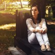 Young woman sitting on a bench in the park — Stock Photo #42148933