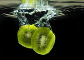 Delicious sliced kiwi dropped in water — Stock Photo