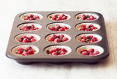 Unripe muffins placed in black tray — Stock Photo