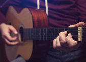 Man playing music at wooden classic guitar — Stock Photo
