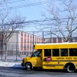 School bus in front of public school - Stock Photo