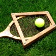 Vintage tennis racket with ball on grass court — Stock Photo