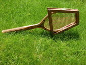 Vintage tennis racket on grass court — Stock Photo