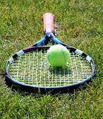 Tennis racket with ball on grass court — Stock Photo