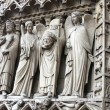 图库照片: St. Denis Decapitated seen at left hand side of main entrance to Notre Dame Cathedral.