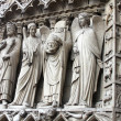 Stock Photo: St. Denis Decapitated seen at left hand side of main entrance to Notre Dame Cathedral.