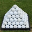 Golf balls pyramid on driving range — Stock Photo