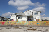 Signs in front of damaged beach house in devastated area four months after Hurricane Sandy on February, 28, 2013 in Far Rockaway, NY — Stock Photo