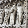 图库照片: St Denis Decapitated seen at left hand side of main entrance to Notre Dame Cathedral