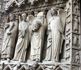 St Denis Decapitated seen at the left hand side of the main entrance to Notre Dame Cathedral — Stok fotoğraf