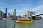 New York City Water Taxi with NYC skyline and Brooklyn Bridge seen from Brooklyn Bridge Park — Stock Photo