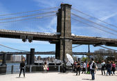 Photographer with the crew shooting young model under Brooklyn Bridge — Stock Photo