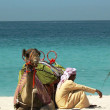 Bedouin with camel on the beach in Dubai — Stock Photo #26069943