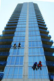 Four window washers on skyscraper — Stock Photo