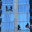 Four window washers on skyscraper — Stock Photo