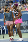 Grand Slam champions Serena Williams and Venus Williams during first round doubles match at US Open 2013 — Stok fotoğraf