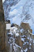 Tourists at the mountain top station of the Aiguille du Midi 3842 m in French Alps watching climbers exercise — Stock Photo