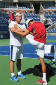 Six times Grand Slam champion Novak Djokovic stretching before practice for US Open 2013 at Billie Jean King National Tennis Center — Stock Photo